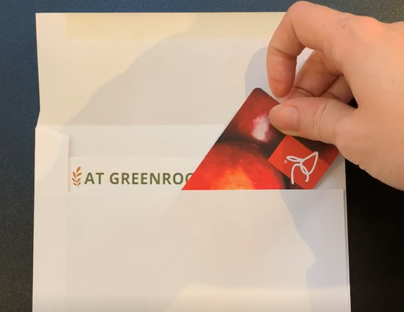 Grocery gift card being packed into envelope